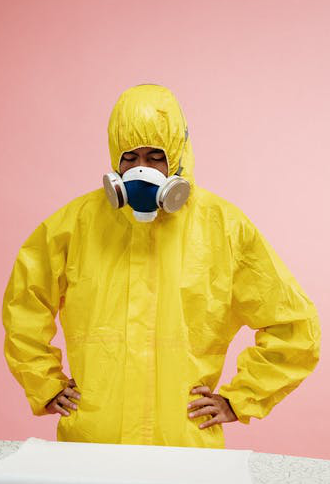An industrial worker wearing a yellow coverall hazmat suit.